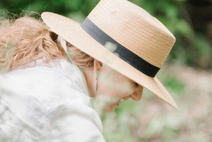 A woman in a wide brimmed straw hat working in a garden.の写真素材 [FYI02254890]