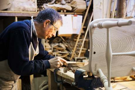 Man standing at a work bench in a carpentry workshop, working on a wooden chair.の写真素材 [FYI02254893]
