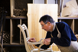 Man standing in a carpentry workshop, working on a wooden chair marking the armrest joint with a penの写真素材 [FYI02254902]