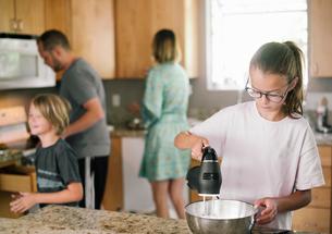 Family preparing breakfast in a kitchen.の写真素材 [FYI02254906]