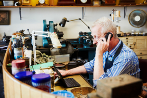 A clock maker busy in his workshop, on his laptop and landline telephone.の写真素材 [FYI02254914]
