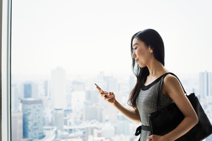 A business woman by a window with a view over the city, using her smart phone.の写真素材 [FYI02254919]