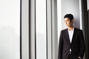 A businessman in the office, by a large window, looking over the city.の写真素材 [FYI02254926]