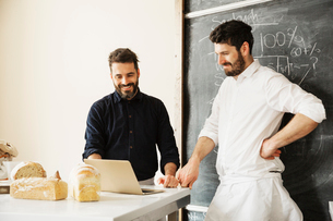 Two bakers standing at a table, using a laptop computer, freshly baked bread, a blackboard on the waの写真素材 [FYI02254932]
