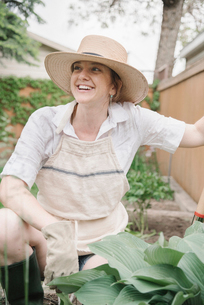 A woman in a wide brimmed straw hat working in a garden, digging.の写真素材 [FYI02254937]