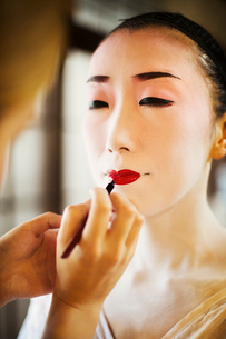 A modern woman creating the traditional geisha vivid red lips by painting on lipstick with a fine brの写真素材 [FYI02254940]