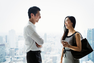 A businessman and businesswoman standing talking by a large window with view over a cityの写真素材 [FYI02254941]