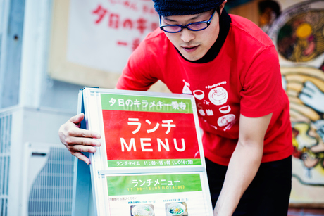 The ramen noodle shop. A man putting out the advertising board and menu on the sidewalk.の写真素材 [FYI02254951]