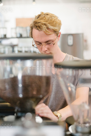 Young blond man with spectacles standing at an espresso machine in a coffee shop.の写真素材 [FYI02254952]
