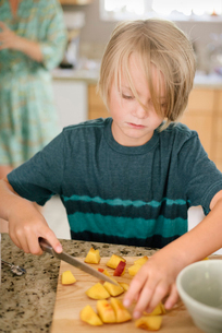 Family preparing breakfast in a kitchen, boy cutting fruit.の写真素材 [FYI02254960]