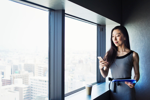 A business woman by a window with a view over the city, using her smart phone.の写真素材 [FYI02254968]