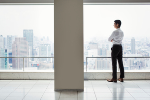 A businessman in the office standing by a large window with arms folded, looking over the city.の写真素材 [FYI02254973]