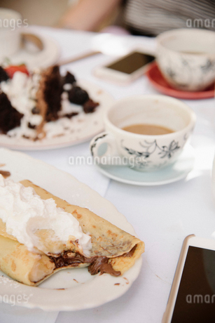 Close up of food and drink on a table, a hot drink, cake and pancake with cream.の写真素材 [FYI02254988]