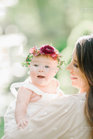 Portrait of a smiling mother and baby girl with a flower wreath on her head.の写真素材 [FYI02254989]