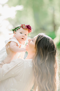 Portrait of a smiling mother and baby girl with a flower wreath on her head.の写真素材 [FYI02254991]