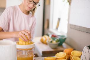 Family preparing breakfast in a kitchen, girl squeezing oranges.の写真素材 [FYI02254996]