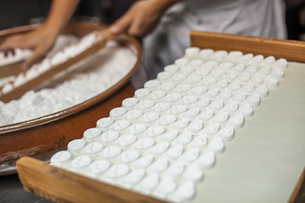 A small artisan producer of wagashi. A man mixing a large bowl of ingredients and pressing the mixedの写真素材 [FYI02255001]