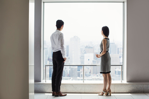 A businessman and businesswoman standing by a large window overlooking a city.の写真素材 [FYI02255005]