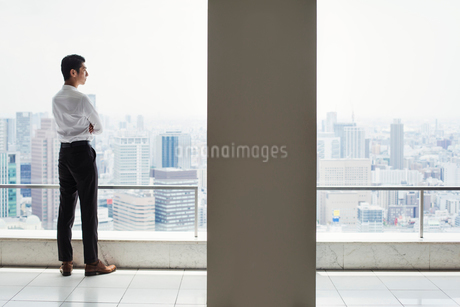 A businessman in the office standing by a large window with arms folded, looking over the city.の写真素材 [FYI02255007]