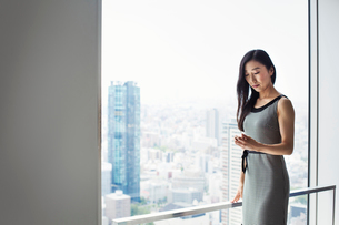 A business woman by a window with a view over the city, using her smart phone.の写真素材 [FYI02255013]