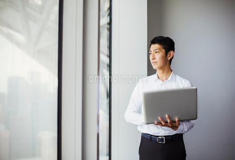 A businessman in white shirt holding a laptop and looking out of a window in a buildingの写真素材 [FYI02255014]