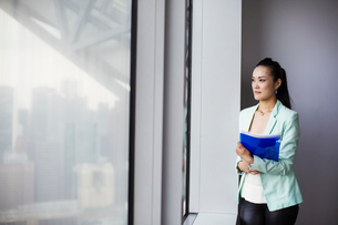 A business woman by a window with a view over the city,の写真素材 [FYI02255021]