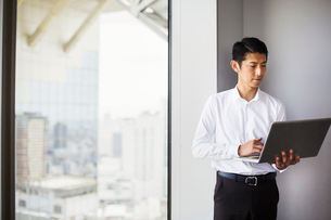 A business man standing by a window with a city view, using his laptop.の写真素材 [FYI02255033]