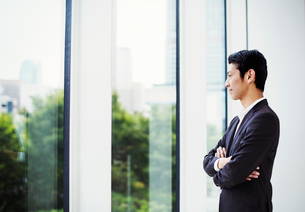 A businessman in the office, by a large window, looking out.の写真素材 [FYI02255034]
