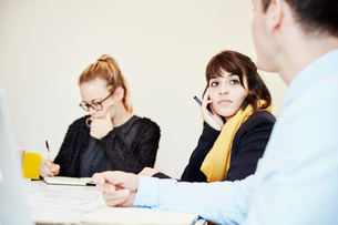 Three people seated at a business meeting, two woman and a man.の写真素材 [FYI02255036]
