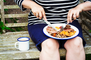 Woman sitting on a bench, eating from a plate of food balanced on her knees.の写真素材 [FYI02255037]