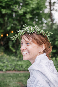 Smiling woman with a flower wreath in her hair sitting in a garden.の写真素材 [FYI02255045]