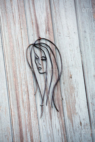 A wire metal sculpture of a woman's face on a wood plank wall.の写真素材 [FYI02255046]