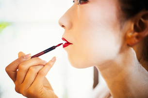 A modern woman creating the traditional geisha vivid red lips by painting on lipstick with a fine brの写真素材 [FYI02255049]