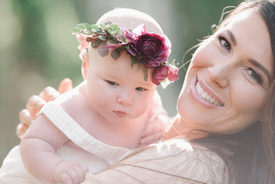 Portrait of a smiling mother and baby girl with a flower wreath on her head.の写真素材 [FYI02255060]