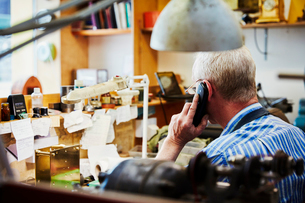 A clock maker on the telephone in his workshop.の写真素材 [FYI02255064]