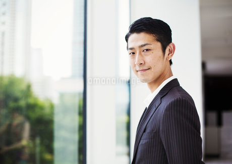 A businessman in the office, by a large window, looking at the camera.の写真素材 [FYI02255067]