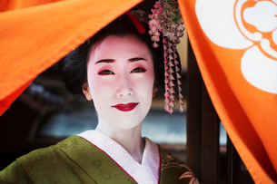 A woman dressed in the traditional geisha style, wearing a kimono with an elaborate hairstyle and flの写真素材 [FYI02255069]