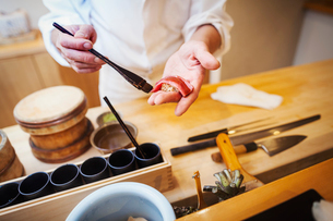 A chef working in a small commercial kitchen, an itamae or master chef making sushi, pasting sauce oの写真素材 [FYI02255074]