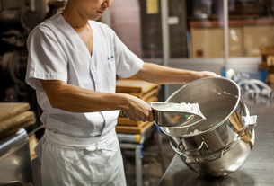 A small artisan producer of wagashi. A man mixing a large bowl of ingredients and pressing the mixedの写真素材 [FYI02255075]