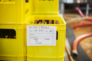 Close up of a yellow plastic crate with beer bottles, a handwritten label.の写真素材 [FYI02255079]