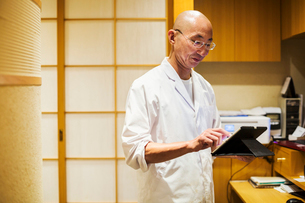 A chef in a small commercial kitchen, an itamae or master chef using a digital tablet.の写真素材 [FYI02255081]