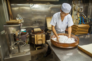 A small artisan producer of wagashi. A man mixing a large bowl of ingredients and pressing the mixedの写真素材 [FYI02255087]