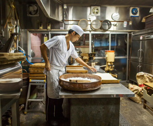 A small artisan producer of wagashi. A man mixing a large bowl of ingredients and pressing the mixedの写真素材 [FYI02255099]