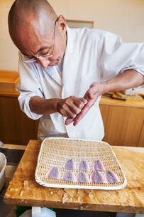A chef working in a small commercial kitchen, an itamae or master chef making sushi, preparing fish.の写真素材 [FYI02255100]