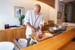 A chef working in a small commercial kitchen, an itamae or master chef slicing fish with a large kniの写真素材 [FYI02255106]