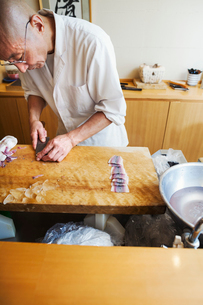 A chef working in a small commercial kitchen, an itamae or master chef slicing fish with a large kniの写真素材 [FYI02255116]