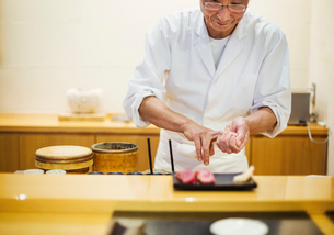 A chef working in a small commercial kitchen, an itamae or master chef presenting a fresh plate of sの写真素材 [FYI02255123]
