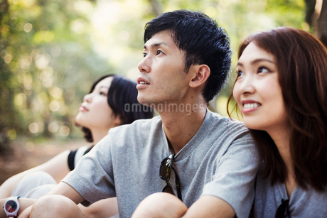 Two young women and a man sitting in a forest.の写真素材 [FYI02255126]