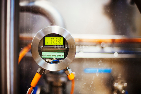 Close up of a gauge with a digital print out in a brewery.の写真素材 [FYI02255127]