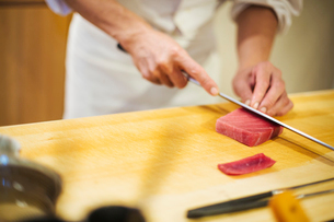 A chef working in a small commercial kitchen, an itamae or master chef slicing fish with a large kniの写真素材 [FYI02255133]